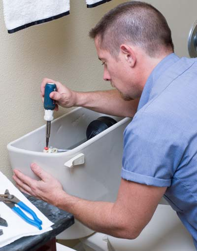 Dutch Enterprises technician working on toilet